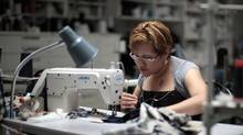 Worker Maria Robles sews clothes at the Karen Kane clothing company in Los Angeles, California June 30, 2011. (LUCY NICHOLSON/REUTERS)