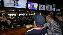 Jason Bryer, left, and Jeremy Pafundi react at they watch a replay of the only team Canada goal against the USA in the Sochi Olympics semifinal match at the Cask 'n Flagon Restaurant and Sports Bar in Marshfield, Mass., Friday, Feb. 21, 2014. Casnada won 1-0. (Stephan Savoia/AP)