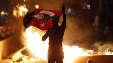 An anti-government protester holds Turkey's national flag with a portrait of Mustafa Kemal Ataturk, founder of modern Turkey, on it during a demonstration in Ankara late on June 2, 2013. (UMIT BEKTAS/REUTERS)