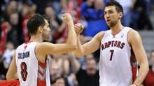 Toronto Raptors forward Andrea Bargnani, right, is congratulated by teammate Jose Calderon after scoring against the Los Angeles Clippers during the second half of their NBA basketball game in Toronto, February 13, 2011. (Reuters)