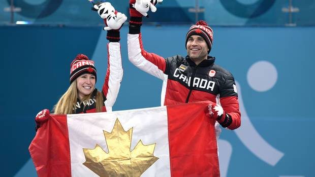 Canada's Kaitlyn Lawes and Canada's John Morris hold the Canada flag on the podium after winning the gold medal in mixed curling at the Pyeongchang 2018 Winter Olympic Games on February 13, 2018.