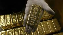 File photo of an employee displaying a bar of one kilogram fine gold at a plant of gold refiner and bar manufacturer Argor-Heraeus SA in the southern Swiss town of Mendrisio November 13, 2008. (Arnd Wiegmann/Reuters)