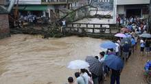 Residents look on amid heavy rainfalls as tree branches are washed down to a bridge by an overflowing river in Shitang township, Guangxi Zhuang Autonomous Region June 21, 2014. (CHINA DAILY/REUTERS)