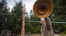A man signals with his hat to those raising a totem pole Thursday in Gwaii Haanas. (John Lehmann/The Globe and Mail)