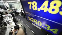 Currency traders at work in a trading house in Japan. (Shizuo Kambayashi/AP)