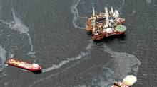 Workboats operate near the Transocean Development Drilling Rig II at the site of the Deepwater Horizon incident in the Gulf of Mexico Friday, July 16, 2010. The wellhead has been capped and BP is continuing to test the integrity of the well before resuming production. (Dave Martin/AP/Dave Martin/AP)