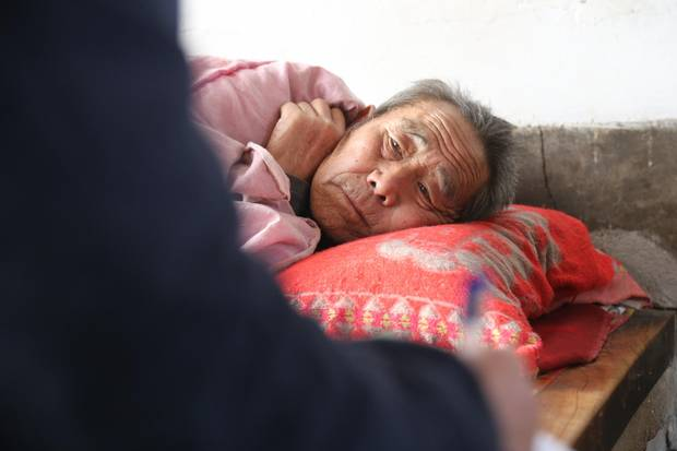 Bed-ridden with bone cancer, Wang Jialing's husband lies in the family home.