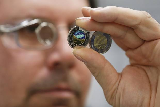 The freshly painted two dollar glow in the dark coin is inspected by production operator Rene Tetrault at the Royal Canadian Mint in Winnipeg Tuesday, April 4, 2017. The Mint in Winnipeg is responsible for the production of all Canadian coins that are put into circulation.