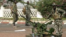 Soldiers stand guard outside the presidential palace after a military coup in Bamako, Mali, on March 23, 2012. (Harouna Traore/AP)
