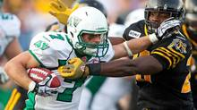 Saskatchewan Roughriders' Weston Dressler tries to break a tackle from Hamilton Tiger-Cats' Jamall Johnson during first half CFL action at Ivor Wynne Stadium in Hamilton, Friday, June 29, 2012. (Geoff Robins/THE CANADIAN PRESS)