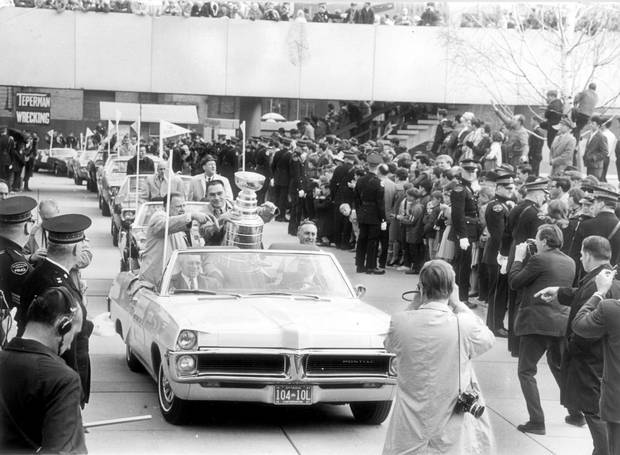 The Toronto Maple Leafs victory parade arrives at City Hall on May 5, 1967, with captain George Armstrong holding the Stanley Cup, escorted by Harold Ballard, executive vice-president of Maple Leaf Gardens and Stafford Smythe, president. (Punch Imlach is in the car behind them.)