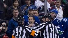 Referees get in the way of Vancouver Canucks head coach John Tortorella as he screams at the Calgary Flames bench during first period NHL action at Rogers Arena in Vancouver, B.C. Saturday, January 18, 2014. (JONATHAN HAYWARD/THE CANADIAN PRESS)