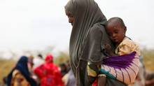 A mother and child wait in the registration area of the Ifo refugee camp, which makes up part of the Kenya's giant Dadaab refugee settlement, on July 19, 2011. (Oli Scarff/Getty Images)