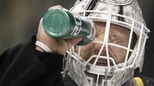 Boston Bruins' Tim Thomas squirts water on his face as he gets ready for a shootout with the Philadelphia Flyers during an NHL hockey game in Boston, Saturday, March 17, 2012. The Bruins won 3-2. (AP Photo/Michael Dwyer) (Michael Dwyer/AP)