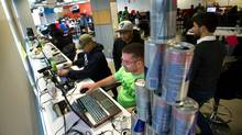 (Front to back) Graeme MacDonald, Evon-Jai Morgan, Jerome Pamintuan and Mike Murray of team Bombard (Behind the cans is XMG's Tekin Salimi) tweak their app during the final few hours of the challenge. Dangerously caffeinated, team Bombard will prove to represent the only trace of enthusiasm during the second day of the Great Canadian Appathon session at Ryerson University's Digital Media Zone. At one point, a particularly animated Bombard member will accidentally smack the team's Red Bull pyramid, sending cans crashing everywhere. He will then giggle uncontrollably for a full minute. (Galit Rodan/Globe and Mail)
