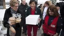 Ontario Premier Kathleen Wynne, left, helps deliver food to the Agincourt Community Centre on Wednesday, Dec. 25, 2013. (Jon Blacker for The Globe and Mail)