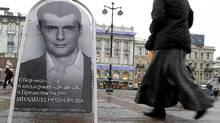 A woman in St. Petersburg passes a board Jan. 11 displaying a portrait of Russian billionaire Mikhail Prokhorov, appealing for his supporters' signatures. Two million are needed for the registration of a presidential candidate, (Alexander Demianchuk/Reuters/Alexander Demianchuk/Reuters)