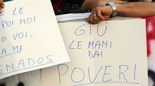 "People show banners reading ""hands off from poors"" outside Italy's Parliament on Aug.11, 2011, ahead of Finance Minister Giulio Tremonti's address. Italy outlined plans for ""very strong"" budget cuts next year including an increase in taxes on investment accounts and cuts in social welfare. (VINCENZO PINTO/AFP/Getty Images)"