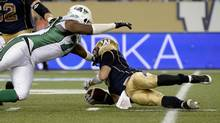 Winnipeg Blue Bombers quarterback Drew Willy (R) is tackled by Saskatchewan Roughriders' Derek Walker during the second half of their CFL football game in Winnipeg Aug. 7. (FRED GREENSLADE/REUTERS)