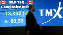 An employee passes a stock board at the Toronto Stock Exchange. (Kevin Van Paassen/The Globe and Mail)
