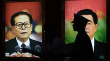 A security guard stands next to pictures of China's former President Jiang Zemin (L) and President Hu Jintao at an exhibition to celebrate the 90th anniversary of the founding of the Communist Party of China (CPC) in Beijing July 7, 2011. (JASON LEE/REUTERS)