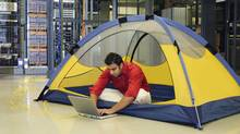 Man in tent using laptop in server room (© 2003 Thinkstock LLC)