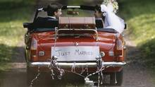 Just married couple departing in a decorated car. (Jupiterimages/Getty Images)