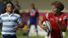 Canada's Conor Trainor, center, sticks out his tongue as Argentina's players run behind as he goes on to score during a men's gold medal rugby match at the Pan American Games in Guadalajara, Mexico, Sunday, Oct. 30, 2011. Canada won the gold and Argentina took the silver. (AP Photo/Jorge Saenz) (Jorge Saenz/AP)