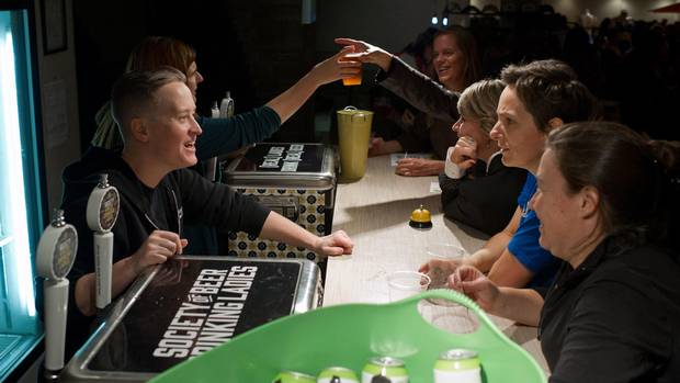 Bartenders Faith McGregor, left, and Katie Brunke serve customers at an event put on by the Society of Beer Drinking Ladies in Toronto on Sept. 30.