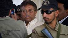 In this Wednesday, April 17, 2013 file photo, Pakistan's former president and military ruler Pervez Musharraf, middle, leaves after appearing in court in Rawalpindi, Pakistan. Pakistan's government plans to put former President Pervez Musharraf on trial for treason. (Anjum Naveed/AP)