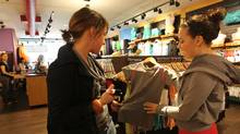 Lululemon employee Laura Struve helps Maureen Eyers (left) with yoga clothing at the Kitsilano store, 2113 W4th Avenue in Vancouver, BC. (Laura Leyshon/The Globe and Mail)