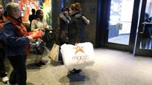 A woman walks out of Macy's department store with shopping bags as the busy holiday shopping season begins in New York, November 17, 2012. (CARLO ALLEGRI/REUTERS)