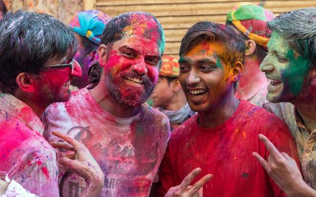 Young men, doused in paint, pose for a photograph.