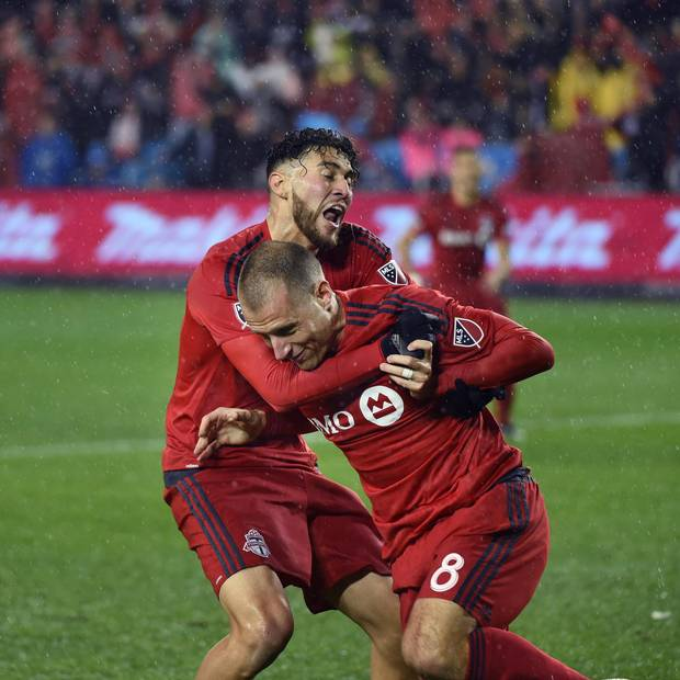 Toronto FC midfielder Benoit Cheyrou gets a hug after scoring the first goal in overtime.