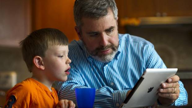 Stephen Hurley and his son Luke, 5, learn about butterflies on an iPad in Milton, Sept. 5, 2012.