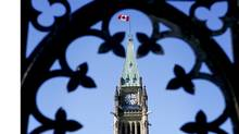 Canada's Maple Leaf flag flies atop a clock tower on Parliament Hill in Ottawa. (BLOOMBERG NEWS)