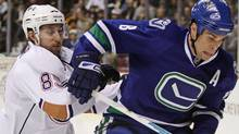 Edmonton Oilers' Sam Gagner, left, and Vancouver Canucks' Willie Mitchell battle for control of the puck during first period NHL action in Vancouver, B.C., on Saturday December 26, 2009. THE CANADIAN PRESS/Darryl Dyck (DARRYL DYCK)