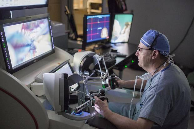 Neurosurgeon Dr. Garnette Sutherland performs a brain surgery using the NeuroArm.