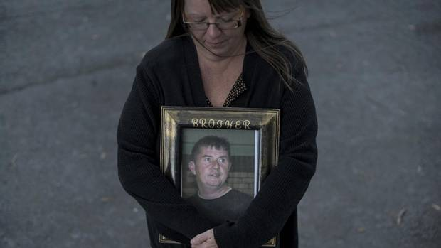 Paulette Raymond cradles a photo of her late brother Tommy who was killed in a work-related accident in 2009