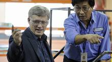 Prime Minister Stephen Harper speaks to a machinist at the Bristol Aerospace plant that will work on the F-35 fighter jets in Winnipeg on Oct. 7, 2010. (FRED GREENSLADE/REUTERS)