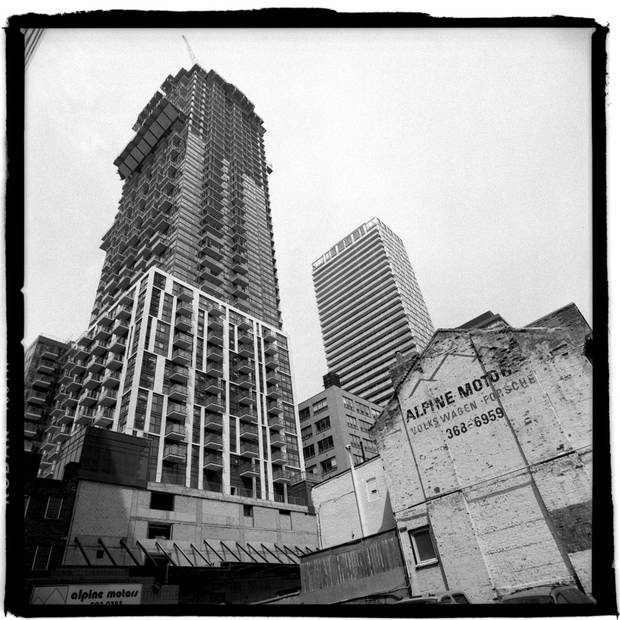 A condo building dwarfs a smaller, older building in Toronto's King-Spadina district, near King Street West and John Street. The neighbourhood is undergoing a massive building boom.
