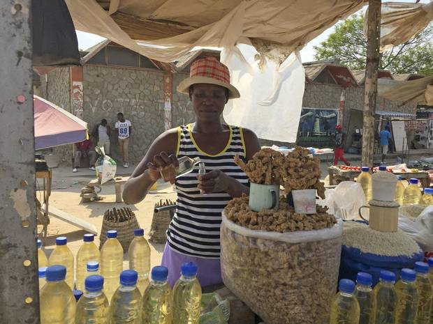 Anna Magaya measures cooking oil into perfume bottles in an outdoor market in the town of Chitungwiza, near Harare.
