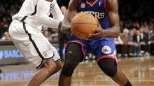 Philadelphia 76ers' Jrue Holiday, right, looks to the basket while Brooklyn Nets' C.J. Watson defends during the second half of an NBA basketball game at the Barclays Center Sunday, Dec. 23, 2012 in New York. The Nets beat the 76ers 95-92. (Seth Wenig/AP)