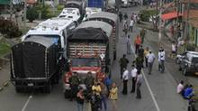 Drivers park their trucks by a road during a protest staged by farmers in Piendamo, Cauca, Feb. 27, 2013. Protests, strikes and bombings across Colombia's commodity sectors have bitten into economic growth. (JAIME SALDARRIAGA/REUTERS)