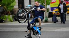 A New York resident attempts a wheelie trying a bicycle as part of a demonstration of a new bicycle sharing system which will start next year, in New York, September 29, 2011. (EMMANUEL DUNAND/AFP/Getty Images)