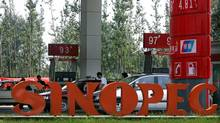 Cars are filled up at a Sinopec gas station in Beijing in this file photo. (Frederic J. Brown/ AFP/Getty Images)