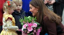 Britain's Catherine, Duchess of Cambridge receives flowers from 3-year old Isobelle Laursen, left, during her visit to Humberside Fire and Rescue Station in Grimsby, north Engalnd, Tues., March 5, 2013. Her Royal Highness met many local people during her visit and people involved in a personal development course run by The Prince's Trust and delivered in partnership with Humberside Fire and Rescue Service. (Owen Humphreys/AP)