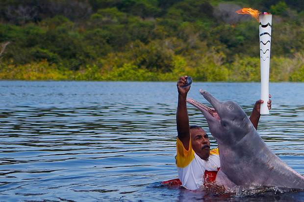 Resident Davi Souza gives a fish to a pink river dolphin as he takes part in the Olympic flame torch relay at Solimoes River in Iranduba city, Brazil, on Monday.