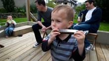 Three-year-old Declan Mehnert, centre right, plays a harmonica as his twin brother Mason Mehnert, far left, plays a tambourine while their parents Richard Abgrall, centre left, and Anthony Mehnert, right, sit in their backyard in Vancouver. (DARRYL DYCK FOR THE GLOBE AND MAIL)