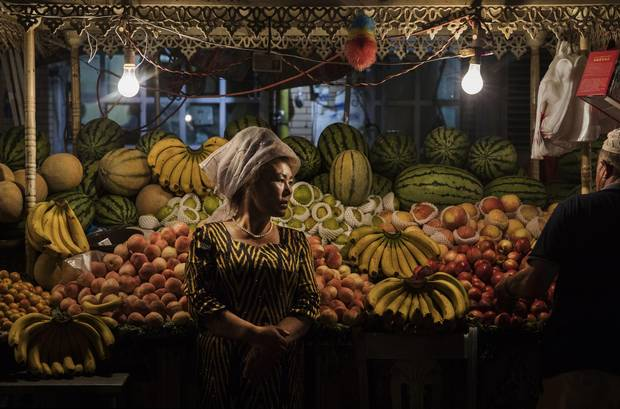 An ethnic Uyghur woman waits for customers at her fruit stand on June 27, 2017 in the old town of Kashgar, in the far western Xinjiang province, China.